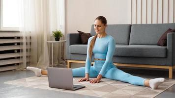 eine schöne frau in einem blauen trainingsanzug dehnt sich foto