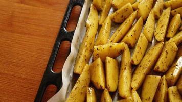 geschnittene rohe Kartoffeln auf einem Backblech mit Gewürzen foto