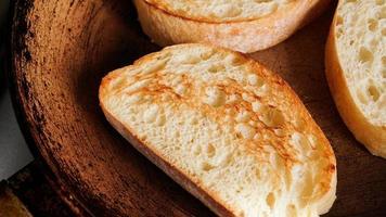 Geschnittenes Ciabatta wird in einer Pfanne gebraten. Scheibe für Bruschetta oder Frühstück. foto