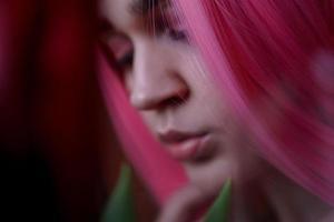 Mädchen mit rosa Haaren mit Blumen nah am Gesicht foto