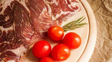 Fleischscheiben und Kirschtomaten. Zutaten foto