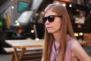 junge Frau mit Sonnenbrille auf dem Hintergrund eines schwarzen Imbisswagens foto