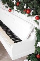 Tasten auf weißem Klavier mit Weihnachtsdekor foto