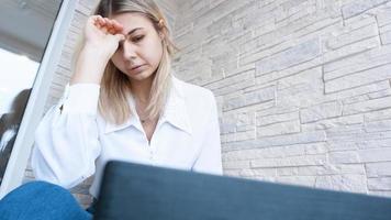 Frau schaut mit gequältem besorgtem Gesichtsausdruck auf ihren Laptop foto