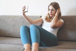 glückliche junge frau, die selfie mit ihrem handy macht foto