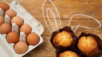 hausgemachter Muffin mit bemalten Hasenohren. Muffin und Eier auf einem Holz foto