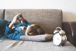 junge Frau, die im Bett telefoniert und auf den Bildschirm schaut foto