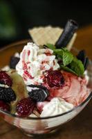 Himbeer-Pistazien-Eisbecher Dessert in Glasschale mit Schokoladenkeksen und Beeren foto
