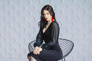 Frau in einem schwarzen Kleid mit roten Ohrringen sitzt auf einem Stuhl foto