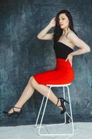 Frau in einem roten Kleid sitzt auf einem Stuhl auf grauem Hintergrund foto