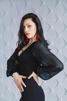 Frau trägt ein schwarzes Kleid, rote Ohrringe im Lichtstudio foto