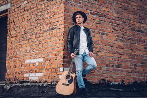 Mann mit Gitarre auf dem Hintergrund einer Mauer foto