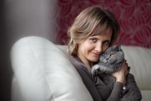 Frau sitzt auf der Couch und streichelt graue Katze foto