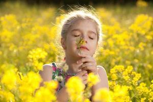 kleines Mädchen genießt den Duft von Blumen foto