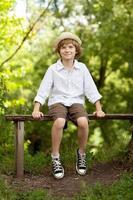 Junge mit Hut und Shorts sitzt auf einer Bank foto