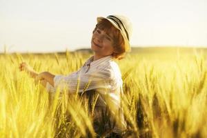 kleiner Junge schüttelt Weizenähren mit den Händen foto