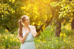 junge glückliche Frau steht mit geschlossenen Augen in einem Garten foto