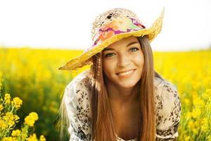 glückliche Frau mit einem Hut aus Wildblumen foto