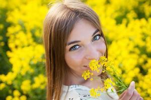 fröhliches Mädchen, das gelbe Wildblumen riecht foto