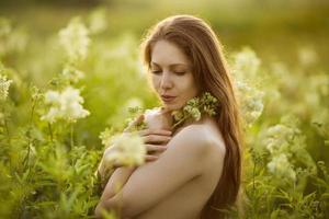 schöne Frau, die in hohen Wildblumen steht foto
