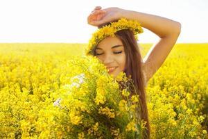 glückliches Mädchen mit einem Strauß Wildblumen foto