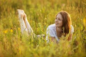 glückliche Frau, die in einem Feld von Gras und Blumen liegt foto