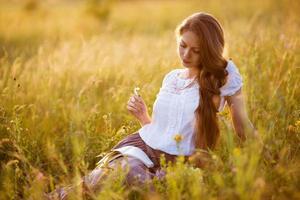 glückliches Mädchen sitzt und liest ein Buch foto