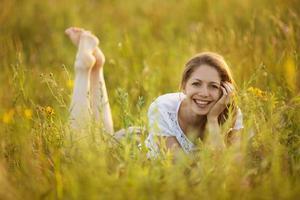 glückliches Mädchen, das im Gras liegt foto