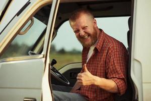 Fahrer des Autos zeigt, dass es ihm gut geht foto