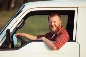 lächelnder Fahrer hinter dem Steuer des Autos foto
