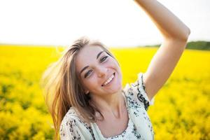 schöne Frau zwischen gelben Blumen auf einem Feld foto