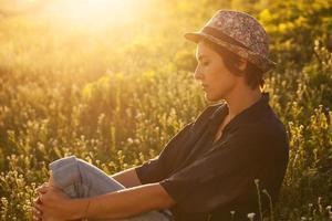 süßes Mädchen, das an einem sonnigen Abend im Gras sitzt foto