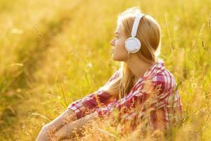 Mädchen mit Kopfhörern sitzt im Gras foto