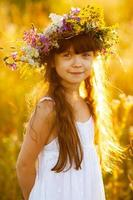 glückliches süßes Mädchen, das einen Blumenkranz trägt foto