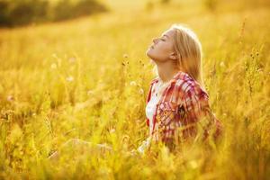 Mädchen mit geschlossenen Augen in Wildblumen foto
