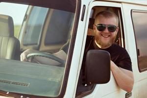lächelnder Fahrer, der ein Auto fährt foto