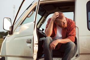 Der Fahrer des Autos sitzt und denkt nach foto