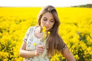 hübsches Mädchen, das gelbe Wildblumen riecht foto