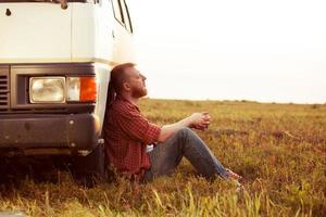 Fahrer ruht auf einem Feld in der Nähe seines Autos foto