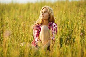 glückliches blondes Mädchen, das auf Gras sitzt foto