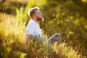 glücklicher Mann, der auf dem Gras sitzt und träumt foto