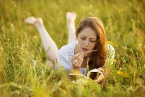 Mädchen mit einem Buch mit Wildblumen foto