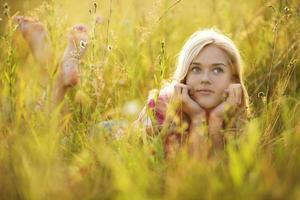 glückliches Mädchen im Gras, das aufschaut foto