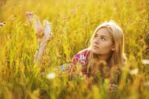 schönes blondes Mädchen, das im Gras liegt foto