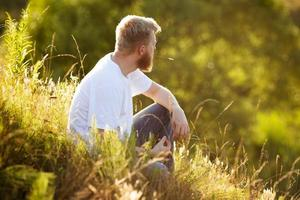 glücklicher Mann, der auf dem Gras sitzt foto