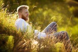 glücklicher Mann auf dem Gras und schaut in die Ferne foto