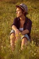 Frau mit Hut sitzt unter Wildblumen foto