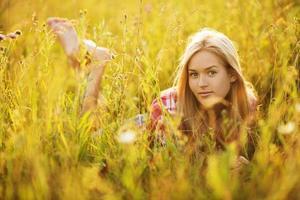 glückliches Mädchen, das zwischen den Wildblumen liegt foto