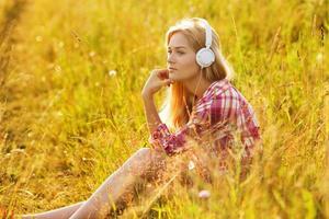 glückliches Mädchen, das Musik über Kopfhörer hört foto