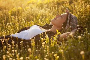 das Mädchen mit Hut dremet zwischen Wildblumen foto